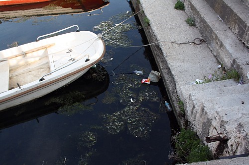 Alexandroupoli (GREECE): Waste in the water at harbour of Alexandroupoli close to fishing boats.